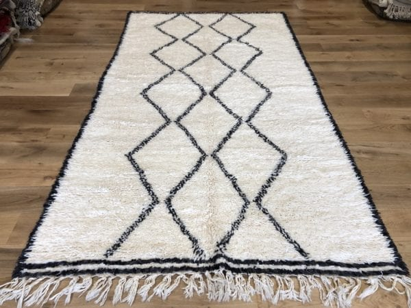 Soft black geometric diamonds are woven on a background of natural ivory white wool